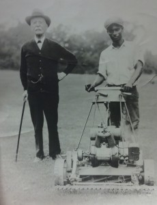 Pat Terry, groundskeeper, poses with Dr. J.E. Booker and the college's first gasoline lawn mower. Read more about Pat Terry's family here.