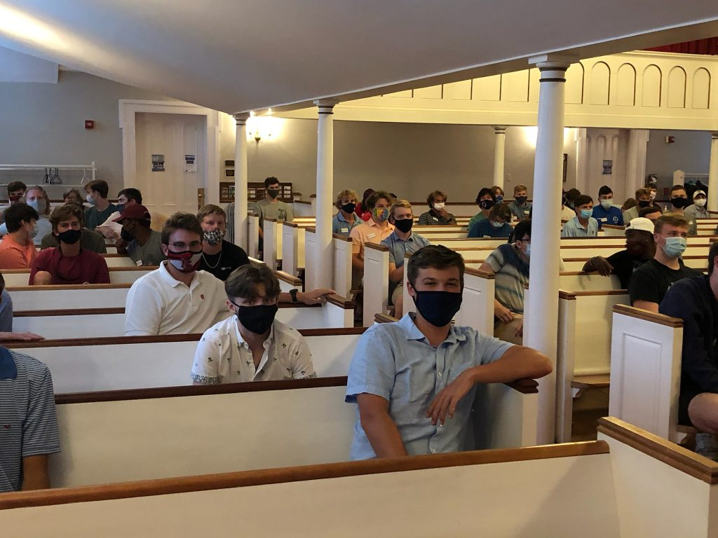 students in a church sanctuary with their masks on